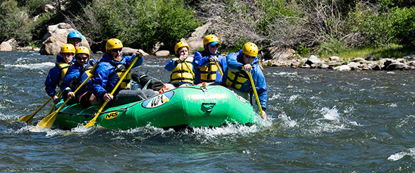 photo of people in a raft in rapids on a river.